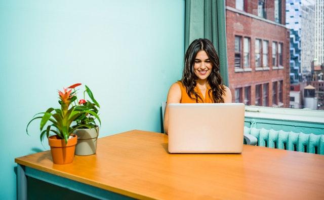 Žena sedí v kancelárii s tyrkysovými stenami a pozerá do notebooku